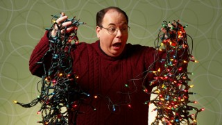 Man overwhelmed by tangled Christmas lights