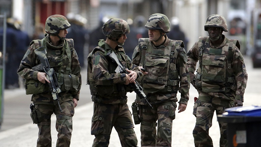 French soldiers stand guard in the northern Paris suburb of Saint-Denis city center, on November 18, 2015, as French Police special forces raid an appartment, hunting those behind the attacks that claimed 129 lives in the French capital five days ago. At least one person was killed in an apartment targeted in the operation aimed at the suspected mastermind of the attacks, Belgian Abdelhamid Abaaoud, and police had been wounded in the shootout.  AFP PHOTO / KENZO TRIBOUILLARD / AFP / KENZO TRIBOUILLARD