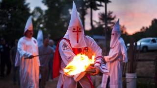Martinsville, 2011. július 2.A Ku Klux Klan (KKK) Lázadó Brigád Lovagjai nevű helyi szervezetének tagjai meggyújtják fákjáikat a keresztégető szertartáson a szervezet egyik tagjának magánbirtokán a Virginia állambeli Martinsville-ben, 2011. július 2-án. Virginia állam területén az utóbbi időben a Ku Klux Klan három helyi szervezete bukkant újra fel, összejöveteleket, keresztégetéseket tartva és új tagokat toborozva. A KKK egy titkosan szerveződő, szélsőséges, amerikai, fehér fajvédő szervezet. A személyazonosságot elfedő köntösökbe, csúcsos maszkokba öltözött tagok összejövetelein elhangzó beszédek visszatérő témája a melegek egyenjogúsága feletti harag, a népesség bőrszín szerinti összetételének megváltozása, és színes bőrű elnök iránti ellenérzés. A KKK tagjai azt mondják, nem gyűlöletről szól a szervezet, hanem csak büszkék saját fajukra. Az első Ku Klux Klant 1865. december 24-én Tennessee államban alapították. (MTI/EPA/Jim Lo Scalzo)