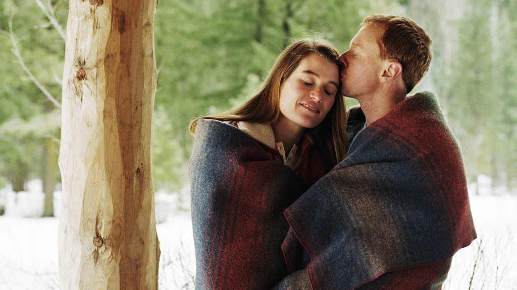 Young couple wrapped in blanket on porch, man kissing woman's forehead