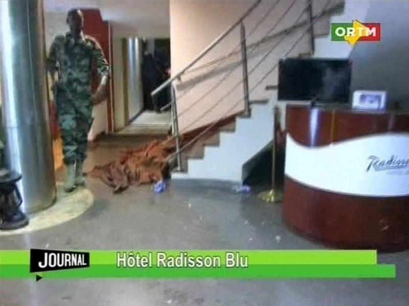 Bamako, 2015. november 20. Tv-felvétel egy letakart holttest mellett elhaladó katonáról a Radisson Blu szállodában Bamakóban 2015. november 20-án. A hotelt dzsihadista fegyveresek támadták meg és százhetven embert túszul ejtettek. (MTI/AP)