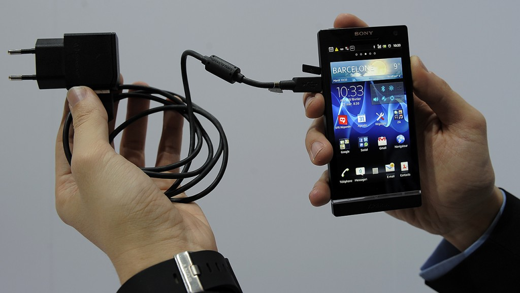 A man displays an universal charger plugged on a Sony mobile phone during a presentation at the Mobile World Congress on February 28, 2012 in Barcelona. The 2012 Mobile World Congress, the world's biggest mobile fair, is held from February 27 to March 1 in Barcelona. AFP PHOTO/LLUIS GENE
