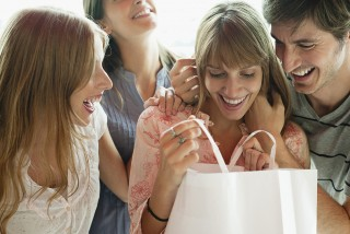 Young woman opening gift from friends