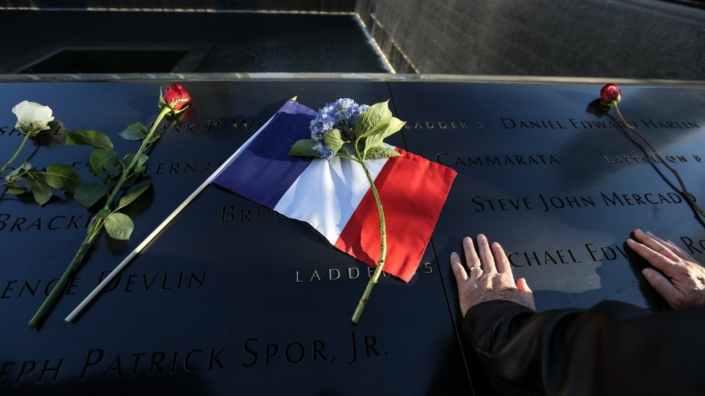 NEW YORK, USA - NOVEMBER 16:  People leave flowers under the Survivor Tree, the National September 11 Memorial & Museum, as they hold a memorial service for the Paris terror attakcs victims, in New York City, United States on November 16, 2015. Cem Ozdel / Anadolu Agency