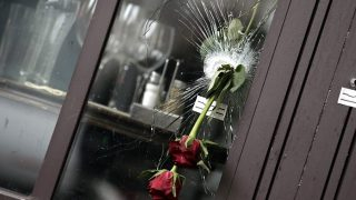 """Flowers are put on bullet holes in the windows of the cafe """"Bonne biere"""", on November 17, 2015  in tribute to the victims of the Paris attacks claimed by Islamic State which killed at least 129 people and left more than 350 injured on November 13. AFP PHOTO / KENZO TRIBOUILLARD"""
