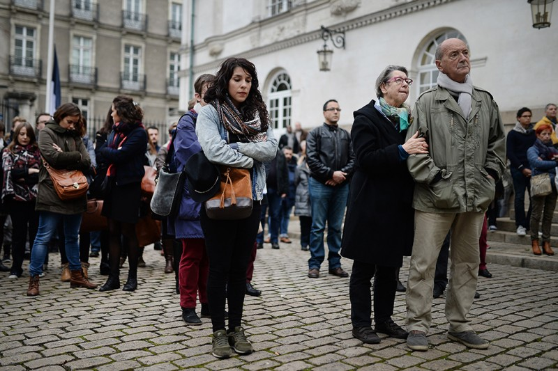 People observe a minute of silence on November 16, 2015 at the cityhall of Nantes, western France to pay tribute to victims of the attacks claimed by Islamic State which killed at least 129 people and left more than 350 injured on November 13.  AFP PHOTO / JEAN-SEBASTIEN EVRARD