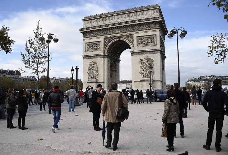People observe a minute of silence at the top of the Champs-Elysees avenue by Arc de Triomphe monument in Paris on November 16, 2015 to pay tribute to victims of the attacks claimed by Islamic State which killed at least 129 people and left more than 350 injured on November 13.  AFP PHOTO / FRANCK FIFE