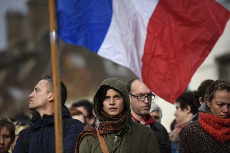 People stand with the French national flag as they arrive to observe a minute of silence on November 16, 2015 in front of the Le Carillon cafe in Paris, to pay tribute to victims of the attacks claimed by Islamic State which killed at least 129 people and left more than 350 injured on November 13. AFP PHOTO / LIONEL BONAVENTURE