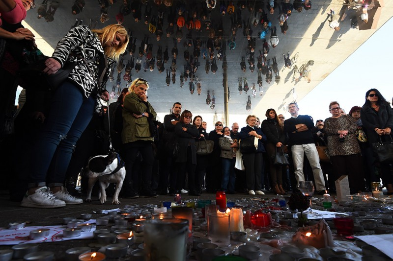 People observe a minute of silence on November 16, 2015 on the old Harbour in Marseille to pay tribute to victims of the attacks in Paris, claimed by Islamic State which killed at least 129 people and left more than 350 injured on November 13. AFP PHOTO / ANNE-CHRISTINE POUJOULAT
