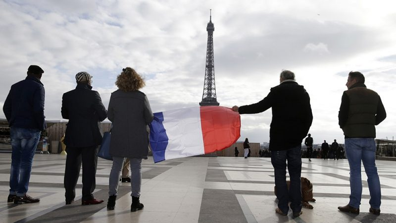 People observe a minute of silence at the Place de Trocadero in Paris on November 16, 2015 to pay tribute to victims of the attacks claimed by Islamic State which killed at least 129 people and more than 350 injured on November 13.     AFP PHOTO /  KENZO TRIBOUILLARD
