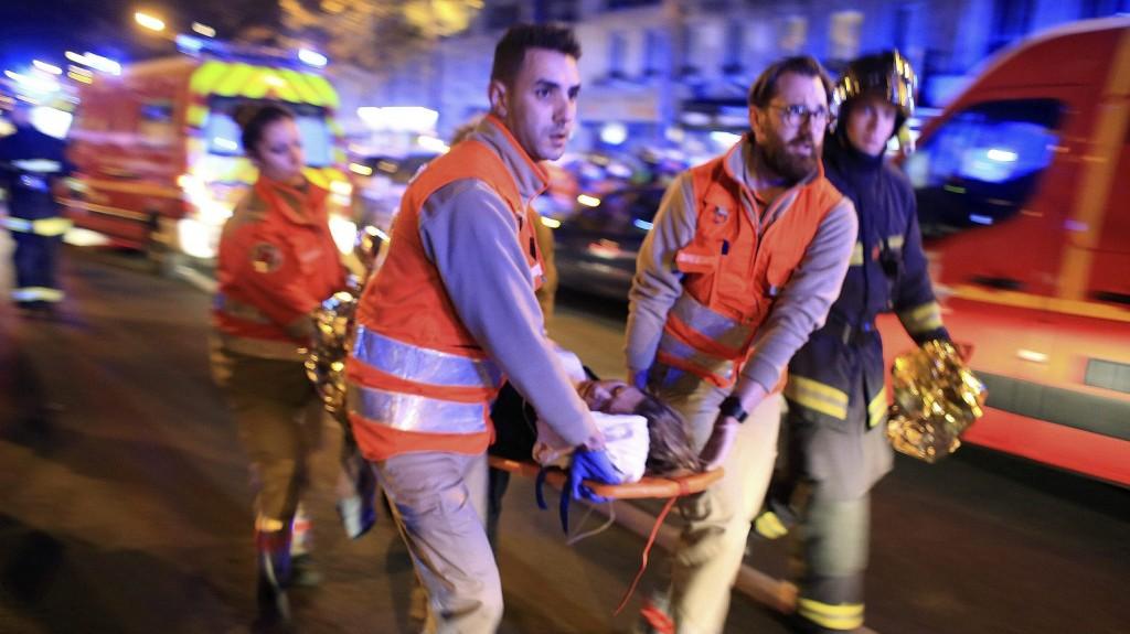 Párizs, 2015. november 14. Mentõalakulatok tagjai menekítik ki a sebesülteket a párizsi Bataclan koncertterembõl 2015. november 13-án. A francia fõvárosban késõ este összehangoltan több merényletet követtek el. A lövöldözésekben és robbanásokban legalább 140 ember meghalt, sokan megsebesültek. Francois Hollande francia elnök egész Franciaország területére rendkívüli állapotot hirdetett és bejelentette a határok lezárását. (MTI/AP/Thibault Camus)