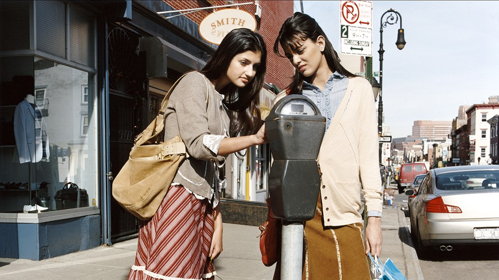 Two Young Women Holding Shopping Bags Operating a Parking Meter on a High Street