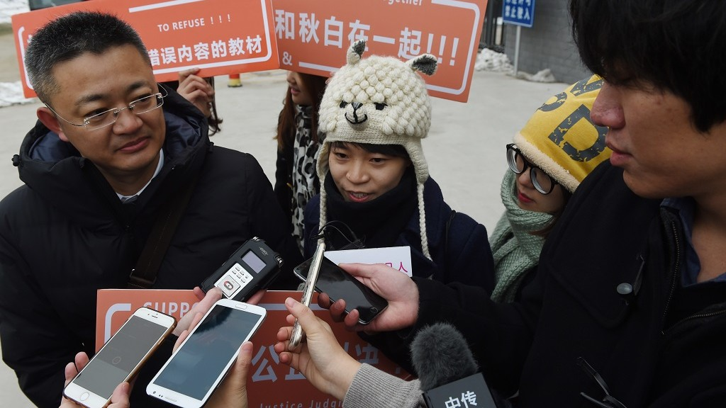 """A Chinese lesbian (C), who goes by the pseudonym Qiu Bai, speaks to the media with her lawyer Wang Zhenyu (L) before entering the Beijing No.1 Intermediate People's Court in Beijing on November 24, 2015. Qiu Bai took the government to court over textbooks describing homosexuality as a """"psychological disorder"""", a landmark case in a country where discrimination remains common.    AFP PHOTO / GREG BAKER / AFP / GREG BAKER"""