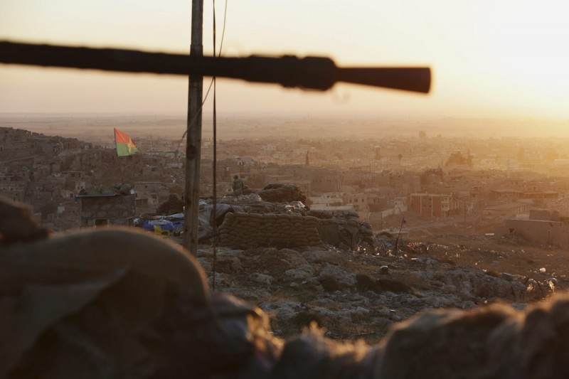 Szindzsár, 2015. november 13. Egy Szindzsár visszafoglalásáért harcoló kurd fegyveres egy kurd zászlóval állásában, az észak-iraki Szindzsár peremén 2015. november 13-án. Ezen a napon a pesmerga néven is ismert kurd fegyveresek a stratégiai jelentõségû város központjából is kiûzték az Iszlám Állam (IÁ) szélsõséges iszlamista szervezet harcosait. (MTI/AP/Bram Janssen)