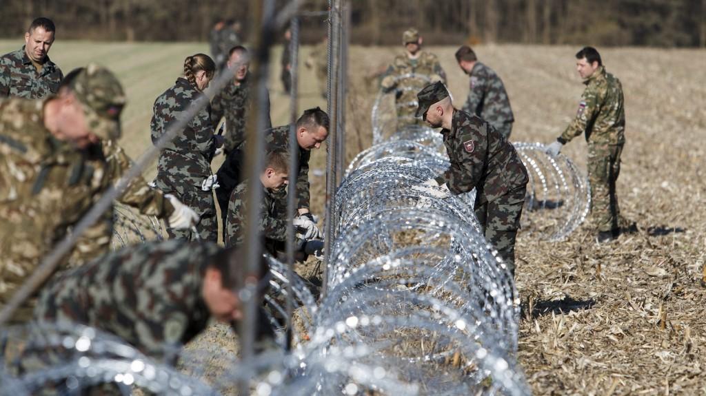 Gibina, 2015. november 11. Szlovén katonák pengésdrótból építenek kerítést a szlovén-horvát határon Gibinánál (Murafüred) 2015. november 11-én. A kerítést az illegális bevándorlók ellenõrizetlen belépésének megakadályozására szánják. MTI Fotó: Varga György