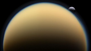 This NASA image received January 27, 2010 shows the heavily cratered Saturn moon Tethys slipping behind Saturn's atmosphere-shrouded Titan in 2009 captured by the robotic Cassini spacecraft orbiting Saturn. The largest crater on Tethys, Odysseus, is easily visible on the distant moon. Titan shows not only its thick and opaque orange lower atmosphere, but also an unusual upper layer of blue-tinted haze. Tethys, at about 2 million kilometers distant, was twice as far from Cassini as was Titan when the above image was taken. / AFP / NASA / HO