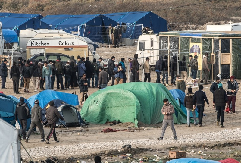 """People walk at the migrant camp known as the """"Jungle"""" in Calais on December 7, 2015. / AFP"""