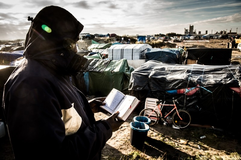"""A man from Sudan reads the Koran at the migrant camp known as the """"Jungle"""" in Calais on December 7, 2015. / AFP / PHILIPPE HUGUEN"""
