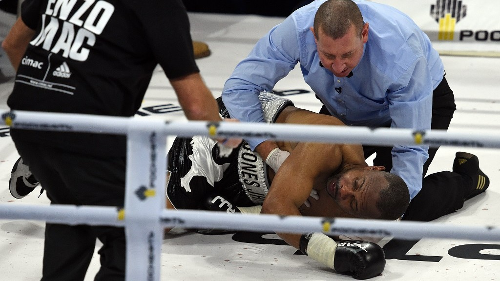 American-Russian boxer Roy Jones Jr. lies in the ring after being knocked out during the bout against British boxer Enzo Maccarinelli in Moscow on December 12, 2015. 46-year-old Roy Jones Jr. has knocked out in first bout as Russian citizen. / AFP / VASILY MAXIMOV