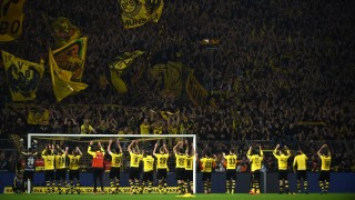 Dortmund's players celebrate with the fans after the German first division football Bundesliga match Borussia Dortmund vs FC Schalke 04 on November 8, 2015, 2015 in Dortmund, western Germany. Dortmund won the derby 3-2. AFP PHOTO / PATRIK STOLLARZ  RESTRICTIONS: DURING MATCH TIME: DFL RULES TO LIMIT THE ONLINE USAGE TO 15 PICTURES PER MATCH AND FORBID IMAGE SEQUENCES TO SIMULATE VIDEO.  ==RESTRICTED TO EDITORIAL USE == FOR FURTHER QUERIES PLEASE CONTACT THE DFL DIRECTLY AT + 49 69 650050. / AFP / PATRIK STOLLARZ
