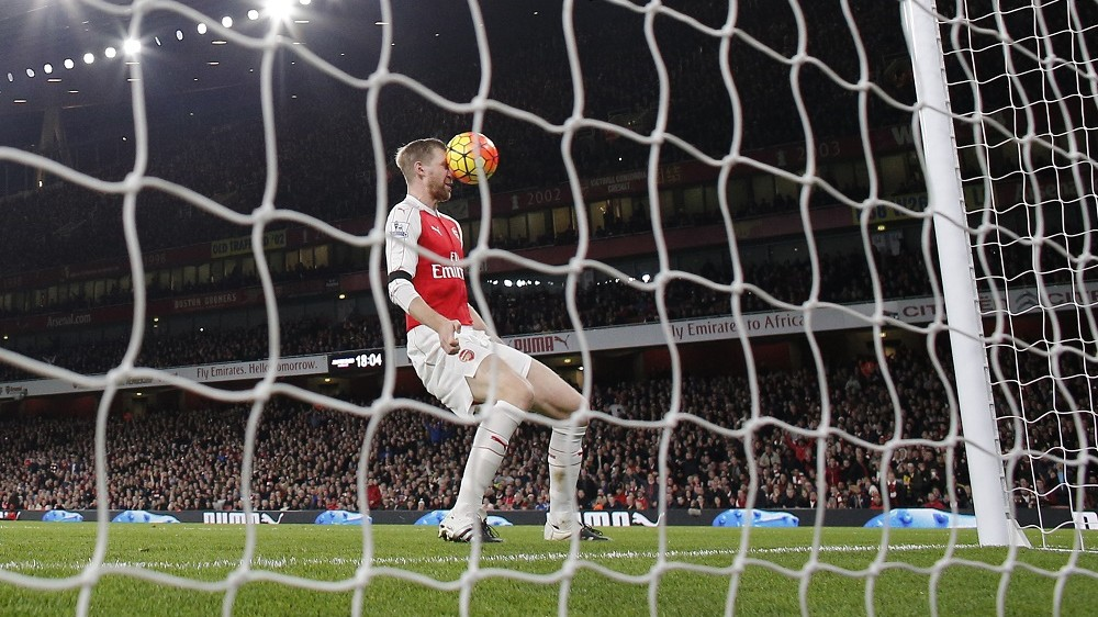 Arsenal's German defender Per Mertesacker cannot direct the ball into the net after it comes off the post during the English Premier League football match between Arsenal and Bournemouth at the Emirates Stadium in London on December 28, 2015. AFP PHOTO / ADRIAN DENNIS  RESTRICTED TO EDITORIAL USE. No use with unauthorized audio, video, data, fixture lists, club/league logos or 'live' services. Online in-match use limited to 75 images, no video emulation. No use in betting, games or single club/league/player publications. / AFP / ADRIAN DENNIS