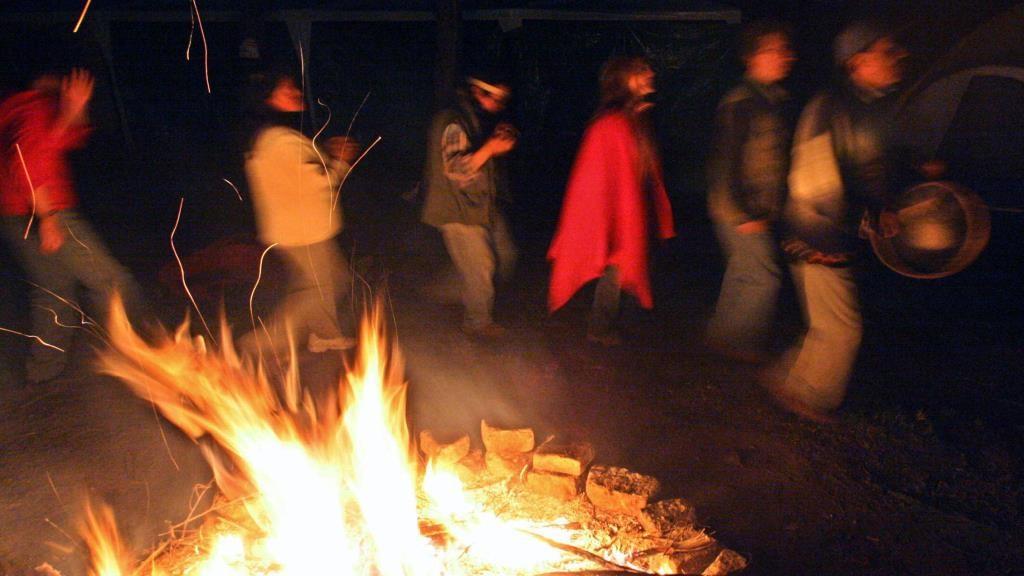 """Hombres y mujeres bailan alrededor del """"fuego sagrado"""" en una ceremonia ritual de la Ayahuasca en el centro ceremonial Quilago en Cochasqui a 30 km de Quito, el 19 de junio de 2005. Esta ceremonia tradicional la realizan los indígenas ecuatorianos para lograr un """"viaje astral"""" o curación con un bejuco o planta de la amazonia llamada ayahuasca. AFP PHOTO/Rodrigo BUENDIA / AFP / RODRIGO BUENDIA"""