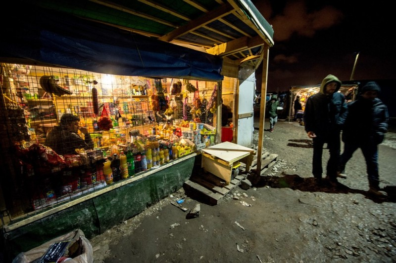 """Refugees and migrants pass a supply shop within the makeshirt camp """"The Jungle"""" on November 25, 2015 in Calais, northern France. Clashes broke out November 25 between some 800 migrants and law enforcement on port bypass Calais (Pas-de-Calais), with seven minor injuries among the police and migrants, according to the prefecture of Pas-de-Calais. AFP PHOTO / PHILIPPE HUGUEN / AFP / PHILIPPE HUGUEN"""