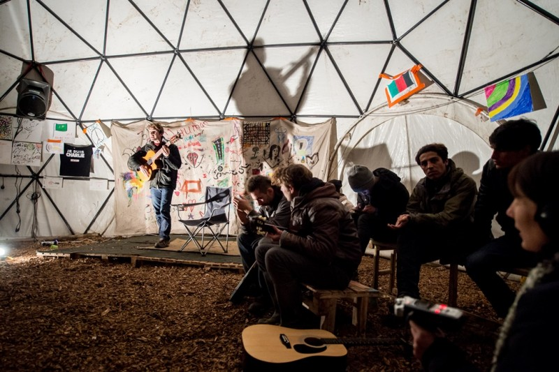 """TO GO WITH AFP STORY BY FIACHRA GIBBONS Migrants listen to a guitarist performing in a makeshift theatre, on November 25, 2015, in the so-called """"Jungle"""" migrant camp in Calais, northern France. AFP PHOTO / PHILIPPE HUGUEN / AFP / PHILIPPE HUGUEN"""