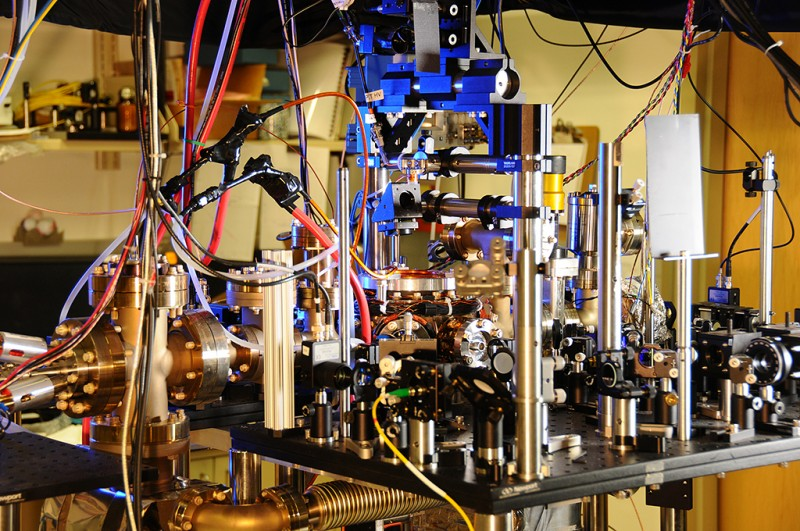 """This photo released August 22, 2013, courtesy of the National Institute of Standards and Technology shows NIST's ultra-stable ytterbium lattice atomic clock. Ytterbium atoms are generated in an oven (large metal cylinder on the left) and sent to a vacuum chamber in the center of the photo to be manipulated and probed by lasers. Laser light is transported to the clock by five fibers (such as the yellow fiber in the lower center of the photo). A pair of experimental atomic clocks based on ytterbium atoms at the National Institute of Standards and Technology (NIST) has set a new record for stability. The clocks act like 21st-century pendulums or metronomes that could swing back and forth with perfect timing for a period comparable to the age of the universe.  NIST physicists report in the August 22, 2013 issue of Science Express that the ytterbium clocks' tick is more stable than any other atomic clock. Stability can be thought of as how precisely the duration of each tick matches every other tick. AFP PHOTO / NIST == RESTRICTED TO EDITORIAL USE / MANDATORY CREDIT: """"AFP PHOTO / NIST / NO MARKETING / NO ADVERTISING CAMPAIGNS / DISTRIBUTED AS A SERVICE TO CLIENTS == / AFP / Burrus/NIST / HO"""