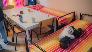 A child of a refugee family from the Balkans lies on a bed at the repatriation facility for Balkan refugees in Bamberg, Germany, 22 October 2015. German interior ministerThomas de Maiziere visited the facility in Bamberg. Photo:NICOLASARMER/dpa