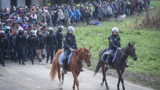 Slovenian mounted policemen escort refugees as they walk towards a refugee camp near the Slovenian-Croatian border in Rigonce, Slovenia on October 20, 2015. After Hungary closed its borders with Croatia, refugees are now traveling to Austria and Germany via Slovenia. Ales Beno / Anadolu Agency