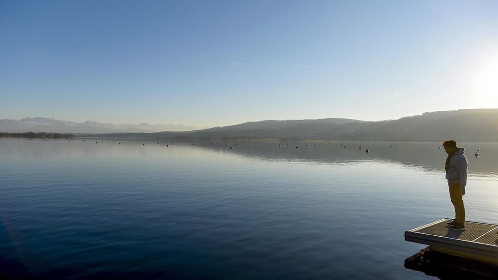 Greifensee, 2015. december 26.Egy férfi a szikrázó napsütésben a Greifensee tó egyik stégjén 2015. december 26-án. (MTI/EPA/Walter Bieri)