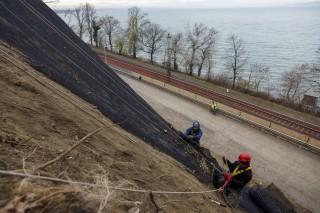 Fonyód, 2015. december 1. Ipari alpinisták védõhálót terítenek le a fonyódi löszfal oldalán 2015. december 1-jén. A 7-es fõút mellett lévõ megcsúszott löszfal helyreállításai munkálatai során kivágták a veszélyes fákat és több mint ezer köbméter fellazult homokot távolítottak el. Az ipari alpinisták közel 1200 négyzetméter védõhálót terítenek le. MTI Fotó: Varga György
