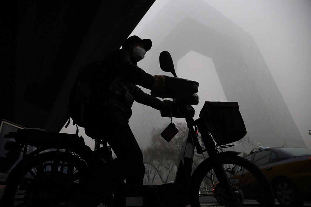 Peking, 2015. december 1.Védőmaszkos motorbiciklis Pekingben 2015. december 1-jén, egy nappal azután, hogy a füstköd miatt a második legmagasabb fokozatú, a narancs színű riasztást rendelték el a kínai fővárosban. (MTI/EPA/Hong Vu)