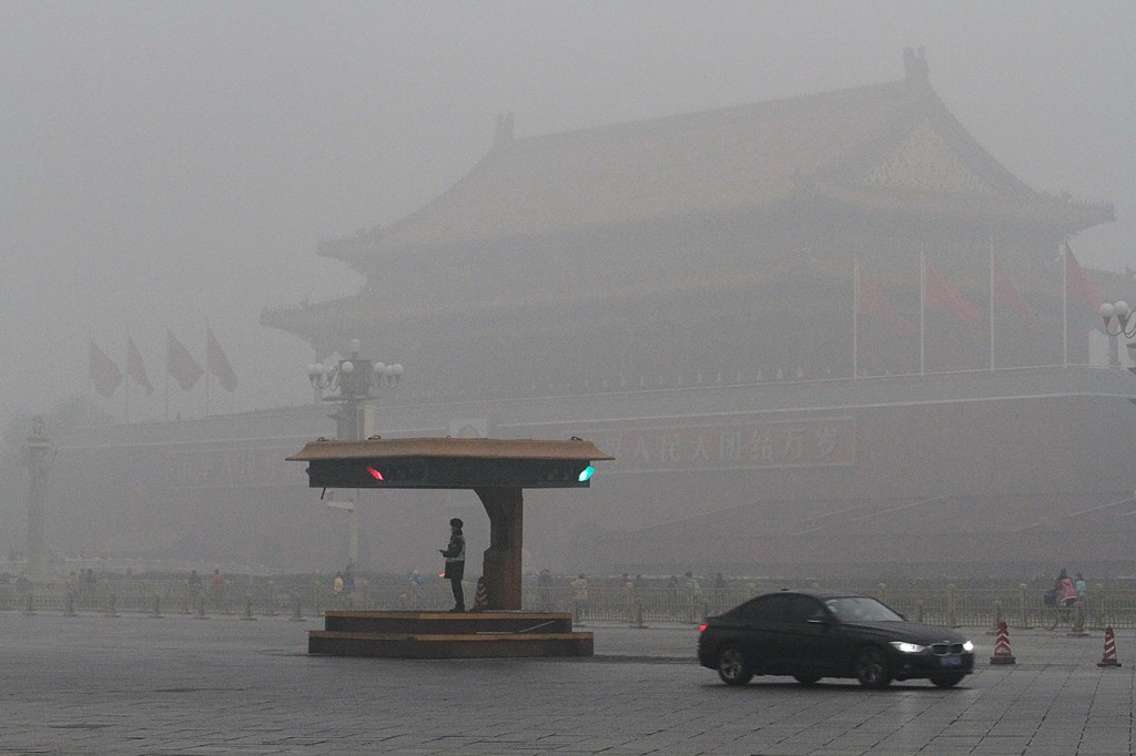 A car passes by a traffic police box in front of the Tiananmen Rostrum in heavy smog in Beijing, China, 1 December 2015.Schools in Beijing were ordered to keep students indoors Tuesday (1 December 2015) after record-breaking air pollution in the Chinese capital soared to up to 35 times the safety levels. The pollution spike is a reminder of China's severe environmental challenges as President Xi Jinping joins other world leaders at the Paris climate conference. Factories and construction sites were told to reduce work after the city government on Sunday issued its first orange alert, the second highest of four warning levels, in almost two years.