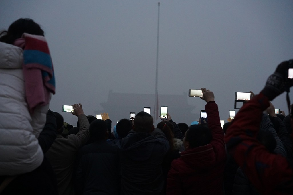People take photos during a flag-raising ceremony on Tiananmen Square in heavy smog in Beijing, China, 1 December 2015.Beijing was again engulfed in heavy smog on Monday (30 November 2015), sending air pollution readings soaring ahead of President Xi Jinping's address to the global climate change summit in Paris. Both the US embassy in Beijing and the municipal government said the air pollution in the capital was at hazardous levels, with the main pollutants in both cases PM2.5 particles, very fine pollutants that are especially harmful to human health. The municipal reading on Monday was roughly 40 per cent higher than that a day earlier. Persistent pollution prompted the authorities to issue the year's first orange pollution alert, the second highest in the four-tier system, on Sunday. The situation was expected to be compounded with traffic authorities forecasting major congestion on the roads partly due to the weather.