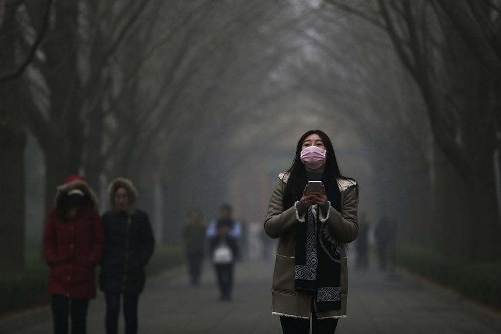 Peking, 2015. november 30.Védőmaszkos nő a pekingi Jung Ho-kung lámatemplom kertjében 2015. november 30-án, amikor füstköd miatt a második legmagasabb fokozatú, a narancs színű riasztást rendelték el a kínai fővárosban. (MTI/EPA/Hou Hvi Jung)