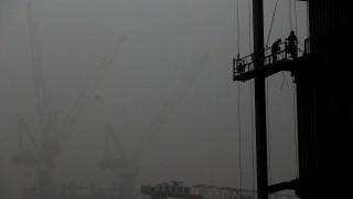 Peking, 2015. december 1.Építőmunkások Pekingben 2015. december 1-jén, egy nappal azután, hogy a füstköd miatt a második legmagasabb fokozatú, a narancs színű riasztást rendelték el a kínai fővárosban. (MTI/EPA/Hong Vu)