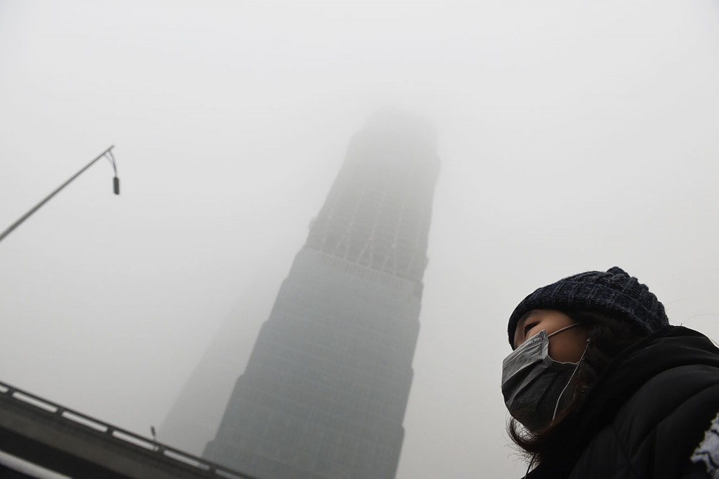 A woman waits for a bus below a skyscraper shrouded in smog on a heavily polluted day in Beijing on December 1, 2015. China has ordered thousands of factories to shut as it grapples with swathes of choking smog that were nearly 24 times safe levels on December 1, casting a shadow over the country's participation in Paris climate talks. A thick grey haze shrouded Beijing, with the concentration of PM 2.5, harmful microscopic particles that penetrate deep into the lungs, climbing as high as 598 micrograms per cubic metre. AFP PHOTO / GREG BAKER / AFP / GREG BAKER