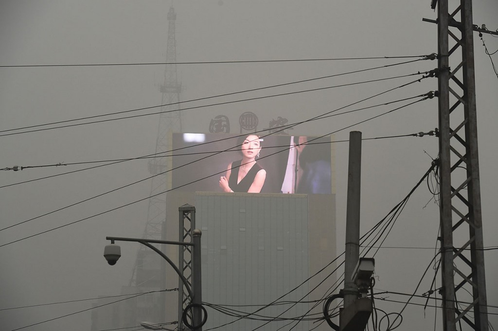 An electronic screen is seen through pollution in Beijing on December 1, 2015. China has ordered thousands of factories to shut as it grapples with swathes of choking smog that were nearly 24 times safe levels on December 1, casting a shadow over the country's participation in Paris climate talks. A thick grey haze shrouded Beijing, with the concentration of PM 2.5, harmful microscopic particles that penetrate deep into the lungs, climbing as high as 598 micrograms per cubic metre. AFP PHOTO / GREG BAKER / AFP / GREG BAKER