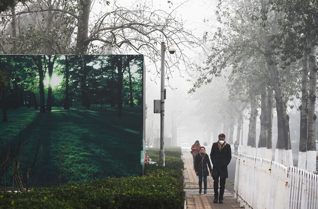 Pedestrians walk past a billboard scene of green trees and grass on a heavily polluted day in Beijing on December 1, 2015. China has ordered thousands of factories to shut as it grapples with swathes of choking smog that were nearly 24 times safe levels on December 1, casting a shadow over the country's participation in Paris climate talks. A thick grey haze shrouded Beijing, with the concentration of PM 2.5, harmful microscopic particles that penetrate deep into the lungs, climbing as high as 598 micrograms per cubic metre. AFP PHOTO / GREG BAKER / AFP / GREG BAKER