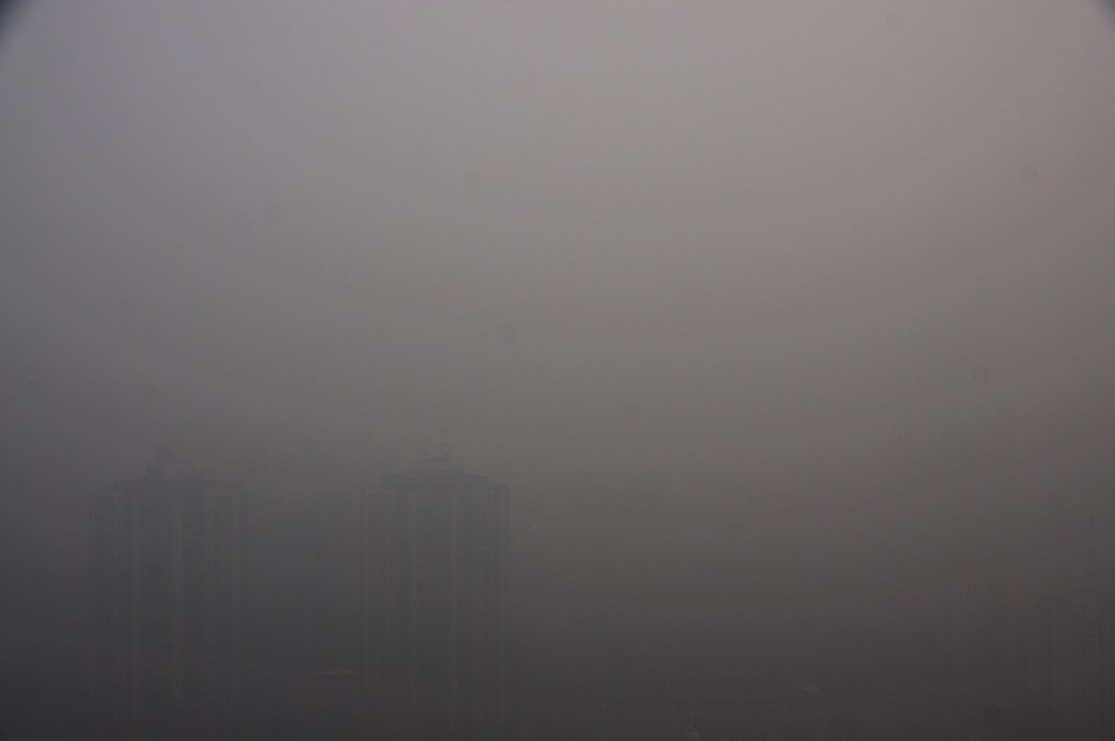 """High-rise buildings are vaguely seen in heavy smog in Beijing, China, 30 November 2015.Beijing issued its highest air pollution alert of the year on Sunday (29 November 2015) as smog persisted in northern China for a second day. Local authorities issued the orange alert, the second highest in the four-tier system, meaning industrial plants were required to cut or shut down production, construction sites should stop transporting materials and waste, and heavy-duty trucks were banned from the roads. The PM2.5 reading hit the """"very unhealthy"""" level of 274 micrograms per cubic metre in most parts of the capital, the municipal weather centre said. The reading at the US embassy in Beijing reached 250 at 10am. The municipal weather centre said humidity and a lack of wind meant the smog would linger for another two days before a cold front arrives on Wednesday."""