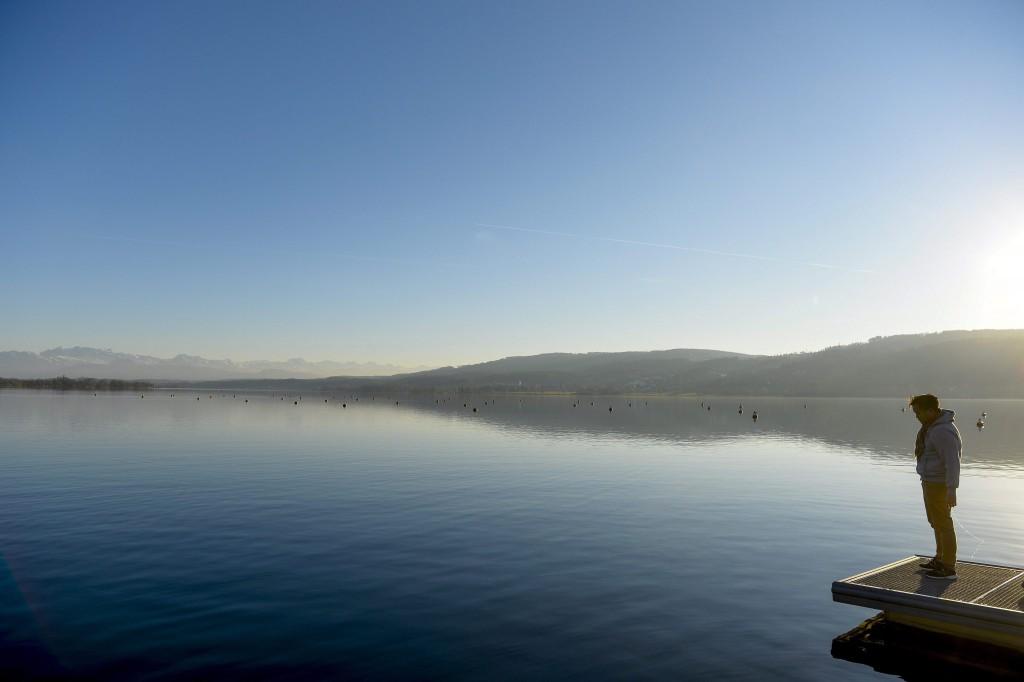 Greifensee, 2015. december 26. Egy férfi a szikrázó napsütésben a Greifensee tó egyik stégjén 2015. december 26-án. (MTI/EPA/Walter Bieri)
