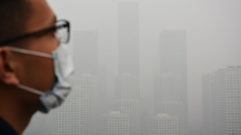 """--FILE--A man wearing a face mask looks at skyscrapers and high-rise buildings in CBD (Central Business District) in heavy smog in Beijing, China, 14 November 2015.China has achieved pollution reduction targets set five years ago with six months to spare, its environment minister said on Sunday (29 November 2015) as international leaders gather in Paris to negotiate reductions in emissions of greenhouse gases that cause dangerous global warming. However, Chen Jining, environment minister, cautioned that China needed a further 30-50 per cent cut in pollutants in order to achieve a """"substantial"""" improvement in its damaged air, soil and water, in a report carried by the state-run Xinhua news agency."""