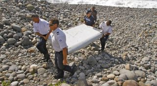 Saint-André, 2015. július 30. Egy repülõgép roncsdarabját viszik rendõrök az Indiai-óceánban elterülõ, Franciaországhoz tartozó Réunion szigetén fekvõ Saint-Andréban 2015. július 29-én. Egy szakértõ szerint a roncsdarab egy Boeing 777-es típusú gépé, de gyelõre nem bizonyított, hogy a 2014. március 8-án eltûnt malajziai utasszállító repülõgép egy darabjával azonos. (MTI/AP/Lucas Marie)