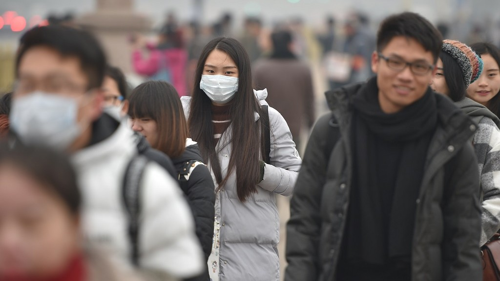 """Pedestrians, most of whom wear face masks, walk on a street in heavy smog in Beijing, China, 8 December 2015.  Much of northern China remains covered by thick hazardous smog as Beijing restricted the use of cars, shut schools and halted outdoor construction after issuing its highest-ever red pollution alert, which came into effect from 7am on Tuesday (8 December 2015). Half of all private cars have been taken off the capital's roads, which led to the Metro trains becoming particularly crowded during the morning rush, state broadcaster CCTV reported. At 11am, the city's air quality index, published by the municipal government, stood at 292 – classified as being a level of """"heavy pollution"""". A number of neighbouring provinces, including Hebei and Henan, are also plagued by heavy smog, with """"heavy pollution"""" or even """"severe pollution"""" levels reported after air quality index readings of more than 300 were recorded. The city of Hengshui, in Hebei, recorded an air quality index level of 500 – the maximum level that can be measured by Chinese authorities."""