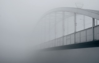 Steel bridge vanishing into fog on cold November morning