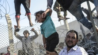 """-- AFP PICTURES OF THE YEAR 2015 --A Syrian child fleeing the war is lifted over border fences to enter Turkish territory illegally, near the Turkish border crossing at Akcakale in Sanliurfa province on June 14, 2015. Turkey said it was taking measures to limit the flow of Syrian refugees onto its territory after an influx of thousands more over the last days due to fighting between Kurds and jihadists. Under an """"open-door"""" policy, Turkey has taken in 1.8 million Syrian refugees since the conflict in Syria erupted in 2011. AFP PHOTO / BULENT KILIC / AFP / BULENT KILIC"""