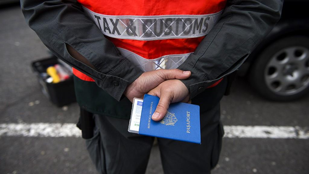 Mosonmagyaróvár, 2013. szeptember 27.A Nemzeti Adó- és Vámhivatal (NAV) pénzügyőre egy útlevelet tart kezében 2013. szeptember 27-én az M1-es autópálya lajtai pihenőjénél, Mosonmagyaróvár közelében, ahol a győri főkapitányság rendőrei a társszervekkel együtt teljes útzáras, komplex közúti ellenőrzést tartottak.MTI Fotó: Koszticsák Szilárd