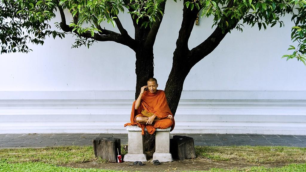 Thailand, Bangkok, Ratanakosin, Wat Mahathat, Buddhist monk sits under tree talking on a cellphone.